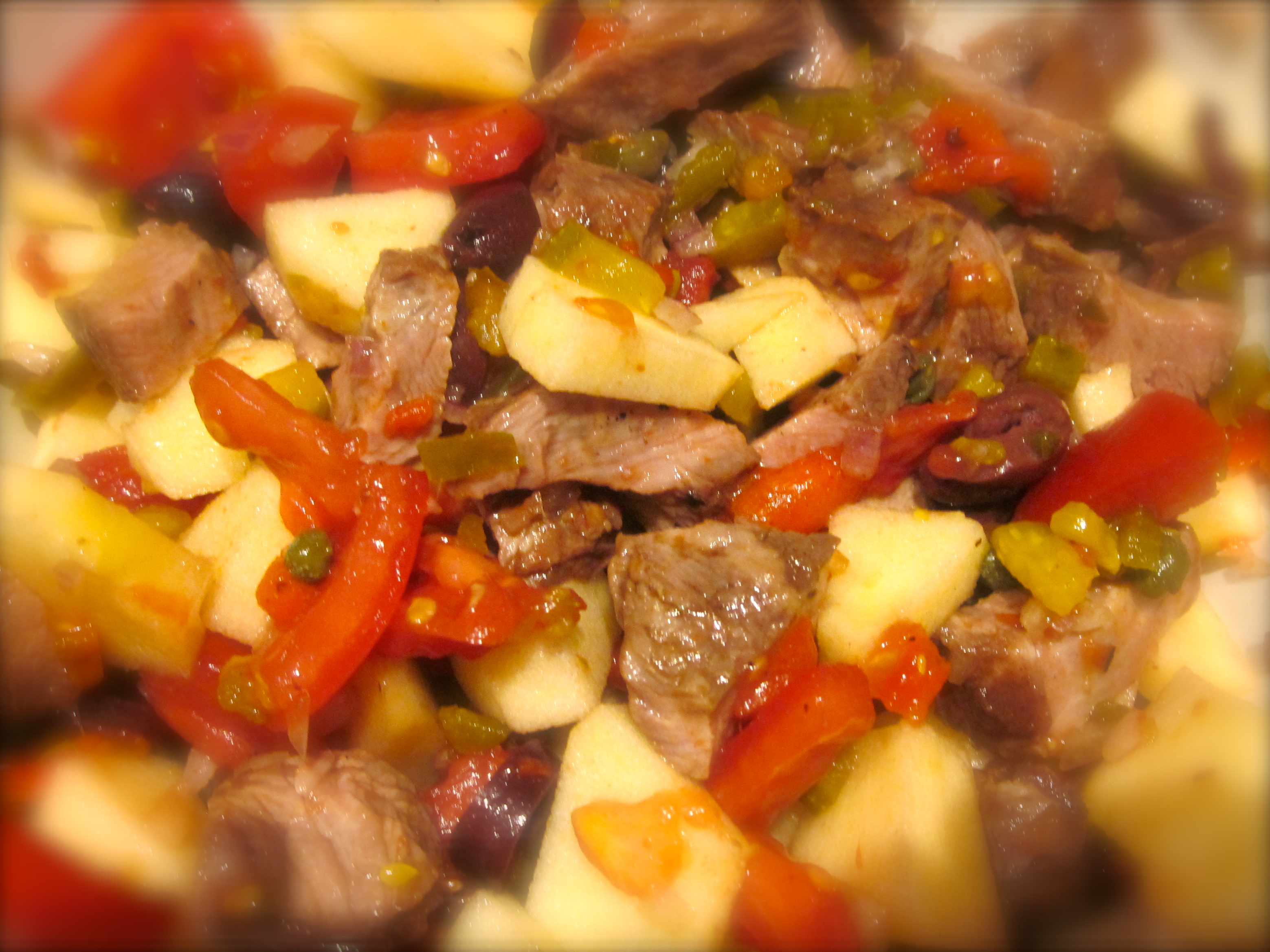 A big bowl of ingredients for my beef salad: diced beef, onions, olives, cornichons, tomatoes, capers, red bell and chile peppers.