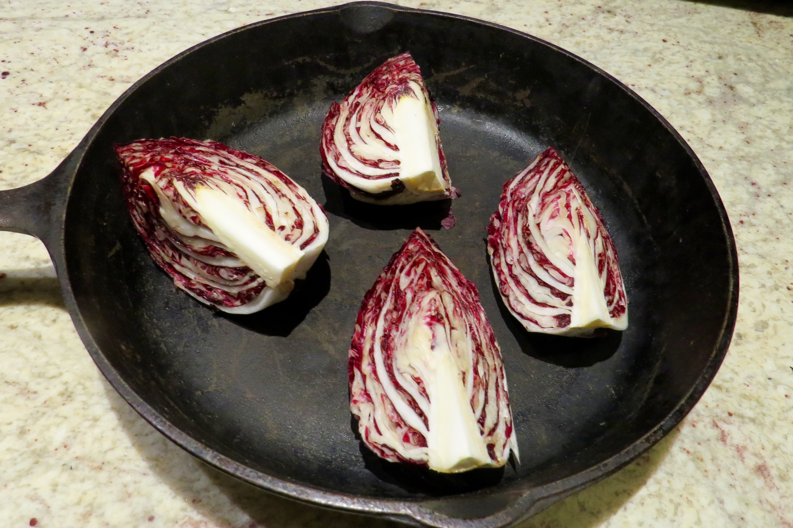 AFTER DRIZZLING EACH RADICCHIO QUARTER WITH OLIVE OIL AND POURING IN WATER, IT'S READY FOR THE OVEN.